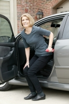 A woman getting out of her minivan pressing up with the handybar stuck into the doorjamb to aid in pushing to standing