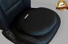 a black pancake-shaped cushion sits on a car bucket seat