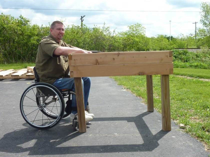 A man using a wheelchair with a raised bed that he can pull his wheelchair under--a tabletop raised bed