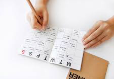 Hands writing in a paper calendar