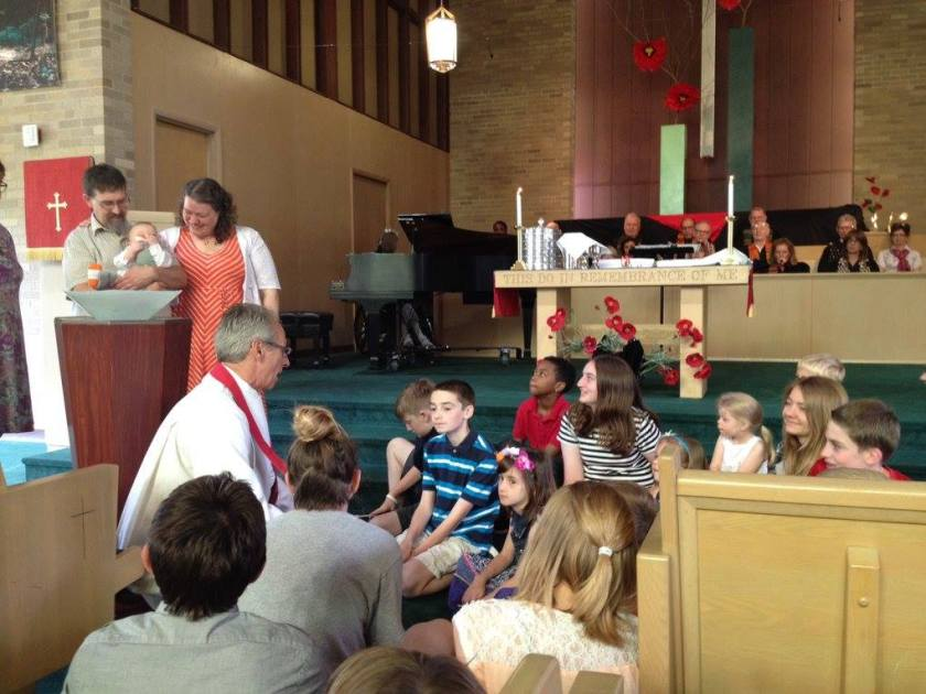 Me next to my husband who is holding our son who is trying to eat his foot. We are next to the baptismal font. Our minister is crouched down in front of it talking to the congregation's children who are gathered around to hear about the meaning of baptism and to welcome Theo.