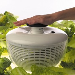 Hand on top of an OXO salad spinner. Lettuce is in the background.