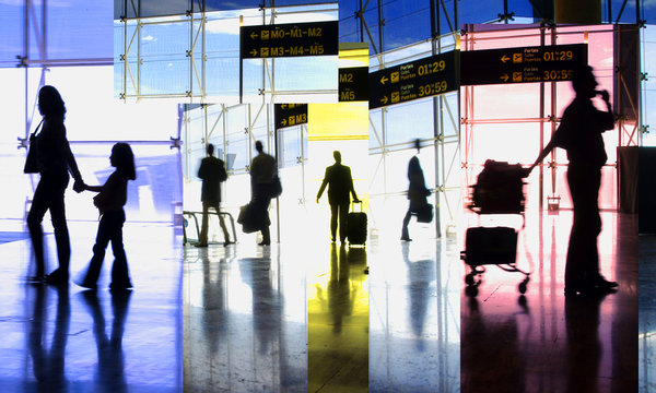shadows of people inside an airline terminal with suitcases and departure signs