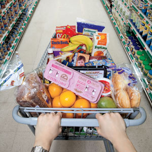 Hands pushing a full grocery cart down a grocery aisle.