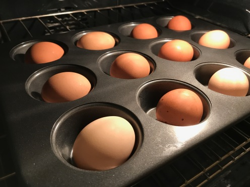 Whole eggs in a muffin pan, inside of an oven