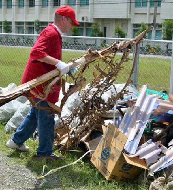 Man in red sweat shirt piling trash in field