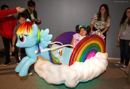 "Girl in her wheelchair that has rainbow wheels, a cloud surrounding the chair, being pulled by a ""My Little Pony"""