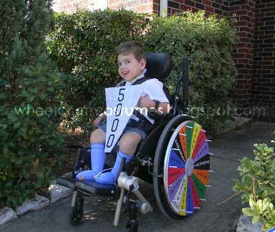 Boy in wheelchair with Wheel of Fortune wheel on his wheel covers. He is holding a $5000 wheel piece.