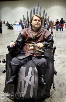 "Young man in a powerchair wearing clothing from the series ""Game of Thrones"". His wheelchair is fashioned to look like the Iron Throne"
