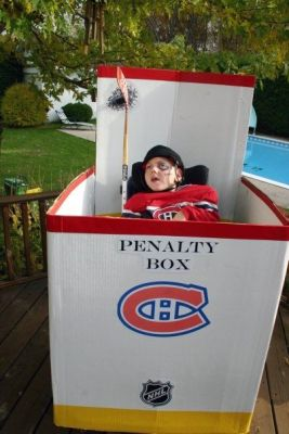 Young child in wheelchair wearing a hockey jersey and holding a hockey stick. His wheelchair is surrounded by a penalty box