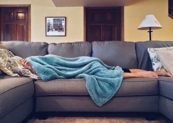 Person laying on a couch with a blanket covering their head and most of their body