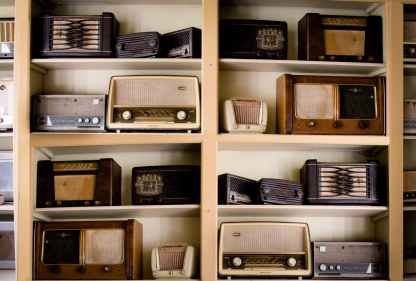 Vintage radios stacked on shelves.