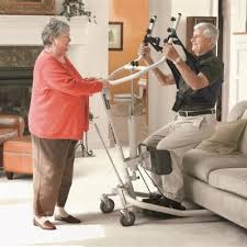 A man and assistant using a sit to stand device