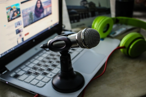 A mic standing on a laptop computer with headphones in the background.