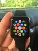 hand holding apple watch with icons of all apps on the face