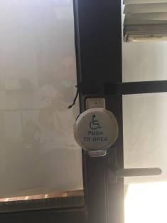 Round accessible power door button pasted over a smaller rectangular button